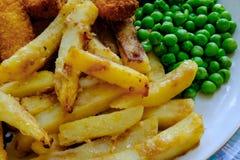 Comida británica tradicional recién preparada de pescado frito con patatas fritas, vista con los guisantes de jardín Imagenes de archivo