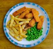 Comida británica tradicional recién preparada de pescado frito con patatas fritas, vista con los guisantes de jardín Fotografía de archivo libre de regalías