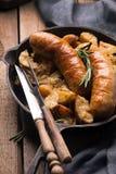 Comida calurosa caliente deliciosa: patatas fritas con las salchichas en la parrilla en una cacerola del arrabio  fotografía de archivo libre de regalías