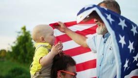 Comida campestre americana preciosa de la familia el 4 de julio Juegos de abuelo con el nieto El beb? se est? sentando en los hom almacen de metraje de vídeo