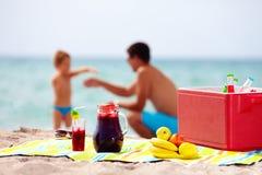 Comida campestre de la familia en la playa Él está mintiendo en cama Imágenes de archivo libres de regalías
