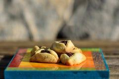 Comida campestre de la primavera en hierba con las galletas hechas en casa en el tablero de madera Galletas de Hamantaschen u o?d fotos de archivo