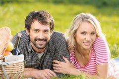 Comida campestre de la primavera. Pares jovenes cariñosos que disfrutan de una comida campestre romántica adentro Imagenes de archivo