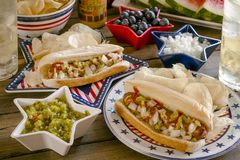 Comida campestre de las vacaciones de verano con los perritos calientes y los microprocesadores imagenes de archivo