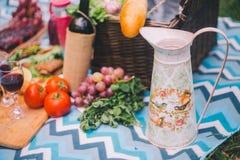 Comida campestre del primer en naturaleza Jarro y comida - verdes, tomates, uvas, vino, baguette imagenes de archivo