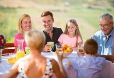 Comida campestre en jardín con la familia feliz Imágenes de archivo libres de regalías