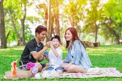 Comida campestre feliz del día de fiesta del niño adolescente asiático de la familia una Fotografía de archivo libre de regalías