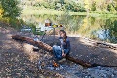 Comida campestre Muchacha cerca de una hoguera Otoño imagen de archivo