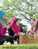 Comida campestre musulmán de la muchacha con el amigo en el parque Imagen de archivo libre de regalías