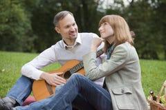 Comida campestre romántica con el hombre que toca la guitarra Imágenes de archivo libres de regalías