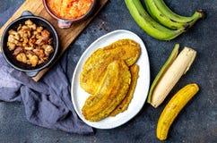 COMIDA CENTROAMERICANA DEL CARIBE COLOMBIANA Patacon o plátano verde entero del toston, frito y aplanado del llantén en blanco imagen de archivo libre de regalías