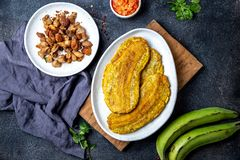 COMIDA CENTROAMERICANA DEL CARIBE COLOMBIANA Patacon o plátano verde entero del toston, frito y aplanado del llantén en blanco foto de archivo