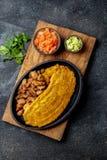 COMIDA CENTROAMERICANA DEL CARIBE COLOMBIANA Patacon o plátano verde entero del toston, frito y aplanado del llantén en blanco imagen de archivo