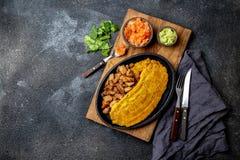 COMIDA CENTROAMERICANA DEL CARIBE COLOMBIANA Patacon o plátano verde entero del toston, frito y aplanado del llantén en blanco fotografía de archivo