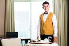 Comida china asiática de la porción del camarero del servicio de habitación en hotel Imagen de archivo