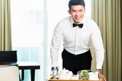 Comida china asiática de las huéspedes de la porción del camarero del sitio en hotel Foto de archivo libre de regalías