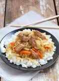 Comida china con arroz, la zanahoria, la col y la carne en la placa negra en fondo de madera Fotos de archivo libres de regalías