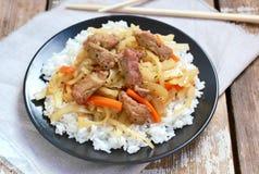 Comida china con arroz, la zanahoria, la col y la carne en la placa negra en fondo de madera Imagen de archivo