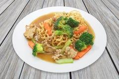 Comida china, tallarines curruscantes del huevo frito con cerdo y zanahoria, bróculi fotografía de archivo libre de regalías