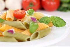 Comida colorida de las pastas de los tallarines de Penne Rigate con los tomates y la albahaca Imagen de archivo