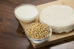 Comida: Cuencos de leche, de sojas y de queso de soja de soja aislados en fondo de madera foto de archivo