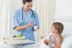Comida de alimentación del doctor a la muchacha enferma Imagen de archivo
