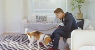Comida de alimentación del hombre joven al perro casero juguetón 4K 4k almacen de video