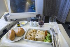 Comida de aviones determinada en una bandeja, en una tabla blanca Imagenes de archivo