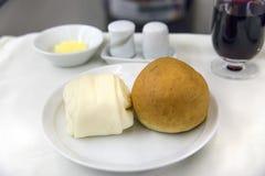 Comida de aviones determinada en una bandeja, en una tabla blanca Imagen de archivo