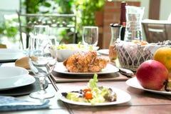 Comida de cena al aire libre completa con el pollo asado, la ensalada, los rollos de pan, el vino y la fruta en verano Fotografía de archivo libre de regalías