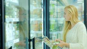 Comida de compra de la mujer atractiva en el supermercado Lea el periódico con ofertas de la publicidad Entonces saque la comida  metrajes
