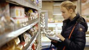 Comida de compra de la mujer en el supermercado que la comprueba con almacen de metraje de vídeo