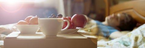 Comida de desayuno de la mañana en la bandeja de madera en la cama del hotel al lado de la persona durmiente f fotos de archivo