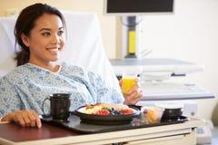 Comida de goce paciente femenina en cama de hospital Foto de archivo libre de regalías