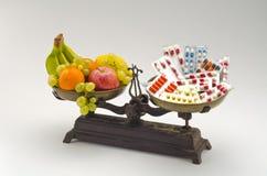 Comida de Healtyy contra píldoras médicas Foto de archivo
