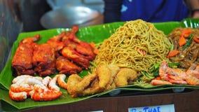 Comida de la calle en el mercado asiático de la noche - tallarines, pollo frito, camarones en la venta para los viajeros metrajes