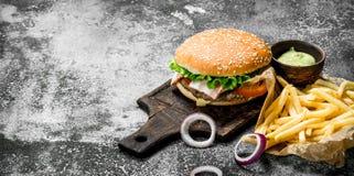 Comida de la calle Hamburguesa con las fritadas y la salsa imagen de archivo libre de regalías