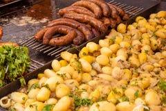 Comida de la calle Las salchichas fritas y las patatas hervidas en mercado atascan Fotografía de archivo libre de regalías