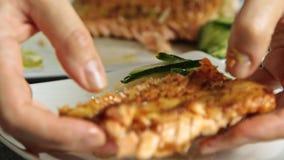 Comida de la mujer que diseña y que cocina los pescados de color salmón con arroz y el pepino metrajes