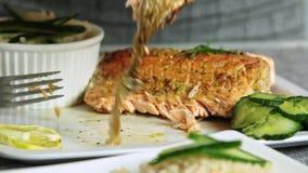 Comida de la mujer que diseña y que cocina los pescados de color salmón con arroz y el pepino almacen de video