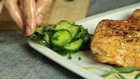 Comida de la mujer que diseña y que cocina los pescados de color salmón con arroz y el pepino almacen de metraje de vídeo