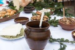 Comida de la Navidad en la tabla que adorna con el árbol de navidad Imagen de archivo libre de regalías