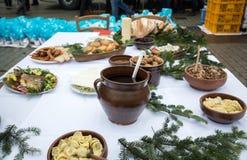 Comida de la Navidad en la tabla que adorna con el árbol de navidad Imágenes de archivo libres de regalías