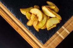 Comida de la patata Patatas cocidas con la sal en la tabla de madera negra Imagen de archivo
