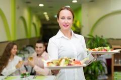 Comida de la porción de la camarera a los visitantes Fotografía de archivo