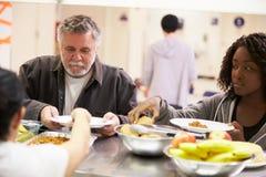 Comida de la porción de la cocina en refugio para personas sin techo Imágenes de archivo libres de regalías
