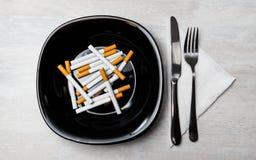 Comida de los cigarrillos con la bifurcación y el cuchillo fotos de archivo libres de regalías