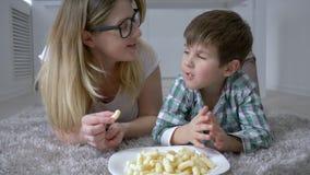 Comida de los niños, niño lindo con la mamá que come los dulces de la placa que miente en piso en casa almacen de metraje de vídeo