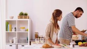 Comida de los pares felices de cocinar y de servicio en casa almacen de metraje de vídeo