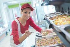 Comida de mantenimiento del trabajador de sexo femenino de la comida fría en cafetería fotografía de archivo